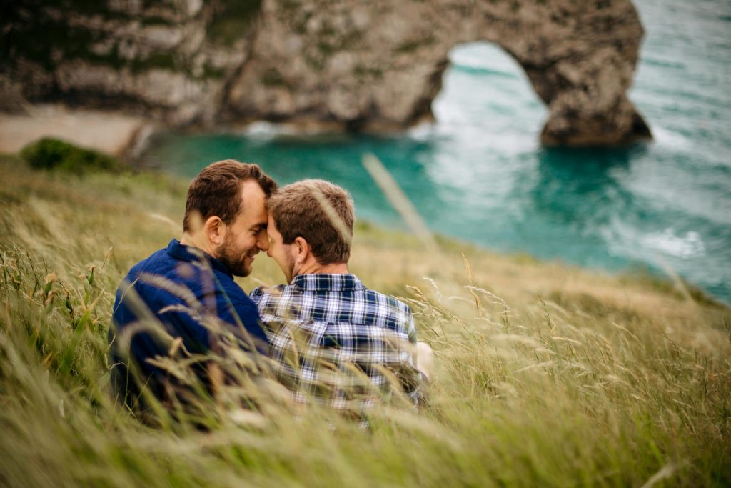 couple embracing with durdle door in background